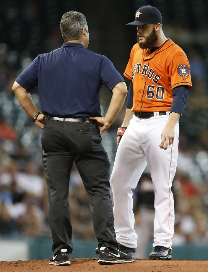 Astros head trainer Nate Lucero checks on Dallas Keuchel after the pitcher was hit by a line drive during the second inning. Photo: Karen Warren, Houston Chronicle