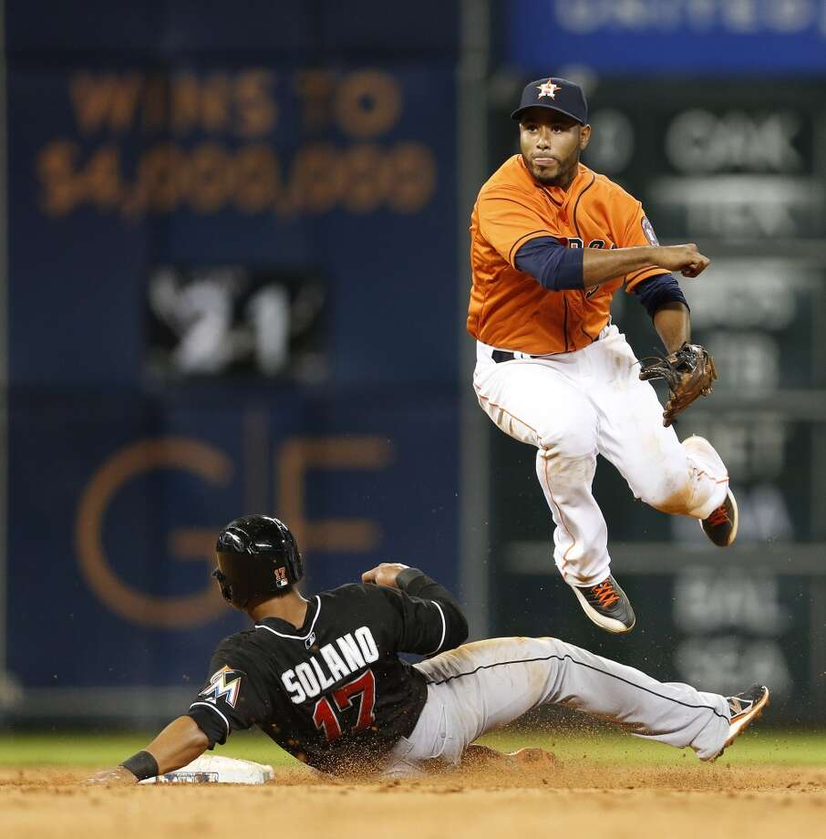 Gregorio Petit leaps over Marlins second baseman Donovan Solano as he throws to first during the sixth inning. Photo: Karen Warren, Houston Chronicle