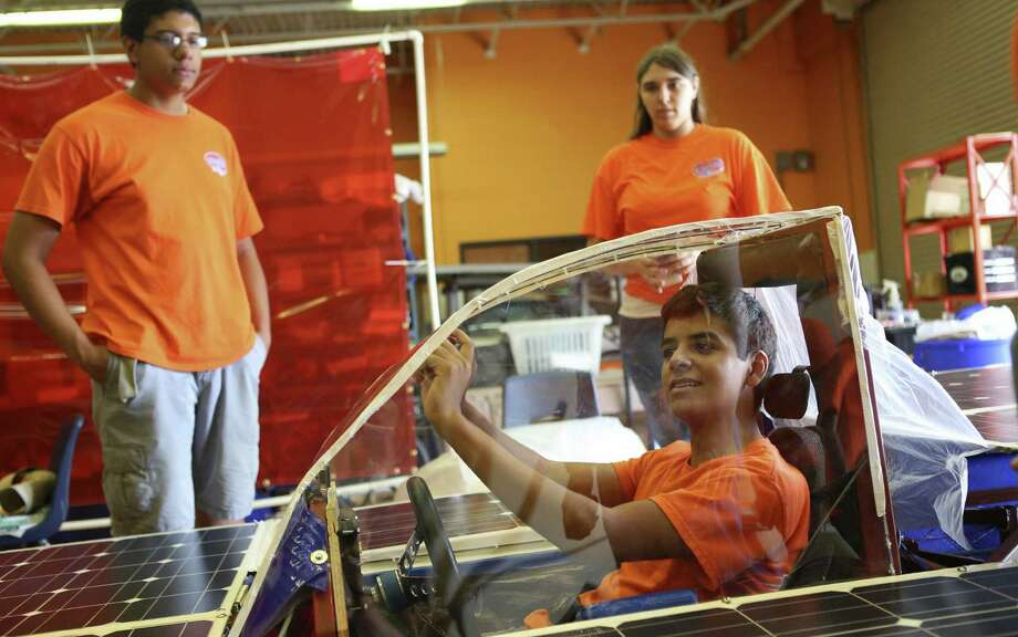 Ricardo Sanchez, 17, adjusts a mirror on the solar car Helios 2 as Jean-Luc Yohi (left), 16, and Skylar Stohner, 17, watch before a test drive at James Madison High School in San Antonio. Photo: Timothy Tai, San Antonio Express-News / © 2014 San Antonio Express-News