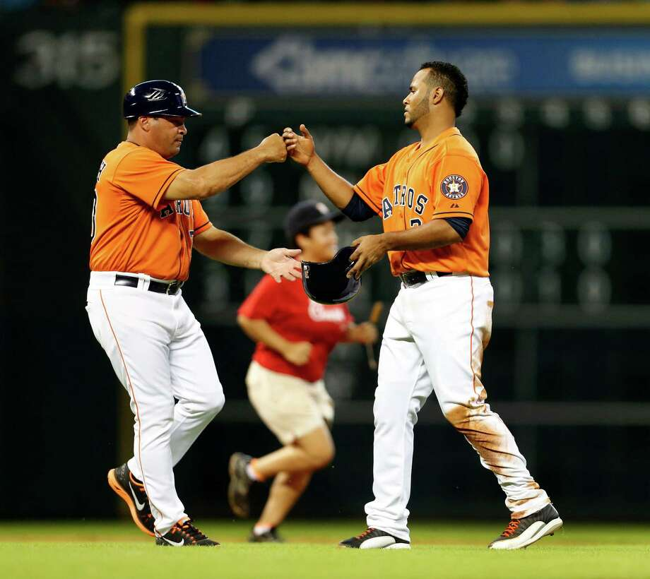 Astros shortstop Gregorio Petit, right, who joined the team after being called up from Oklahoma City, earns a fist bump from third-base coach Pat Listach after getting a single in the third inning Friday night. Photo: Karen Warren, Staff / © 2014 Houston Chronicle