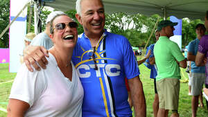 Former Major League Baseball player and manager Bobby Valentine poses for a photo with Lori Slavin, of Fairfield, after taking part in the annual CT Challenge charity bike ride held at Fairfield County Hunt Club in Westport, Conn. on Saturday July 26, 2014. About 1000 riders gathered as individuals and in teams to raise money to help cancer survivors. There were several routes riders took part in, from 10 miles up to 100 miles.
