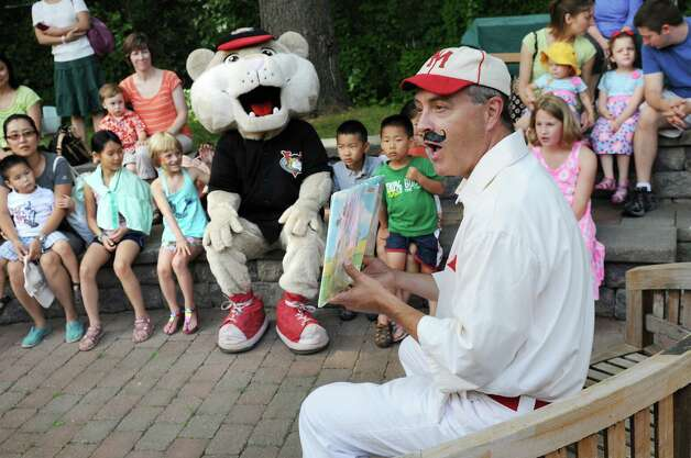 Library director Tim Wiles, dressed as Casey at Bat, right, reads a story to children and SouthPaw, ValleyCats mascot, during Family Fun Day on Saturday, July 26, 2014, at the Guilderland Public Library in Guilderland, N.Y. The event included games, window painting, chalk art, snacks and prizes. (Cindy Schultz / Times Union) Photo: Cindy Schultz / 00027911A