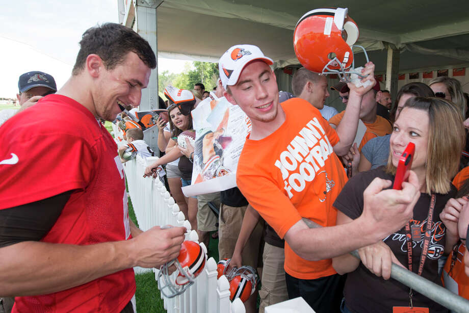 Quarterback Johnny Manziel #2 of the Cleveland Browns signs autographs as a fan takes a selfie during training camp at the Cleveland Browns training facility on July 26, 2014 in Berea, Ohio. Photo: Jason Miller, Getty Images / 2014 Getty Images