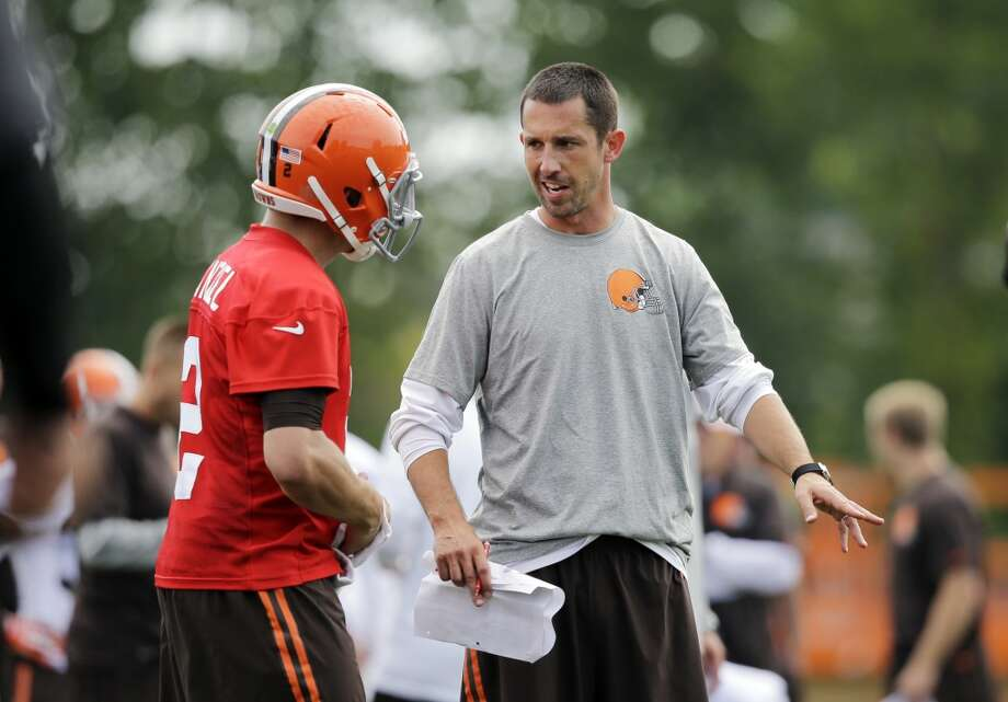 Cleveland Browns offensive coordinator Kyle Shanahan talks to quarterback Johnny Manziel at the NFL football team's training camp in Berea, Ohio Saturday, July 26, 2014. Photo: Mark Duncan, Associated Press