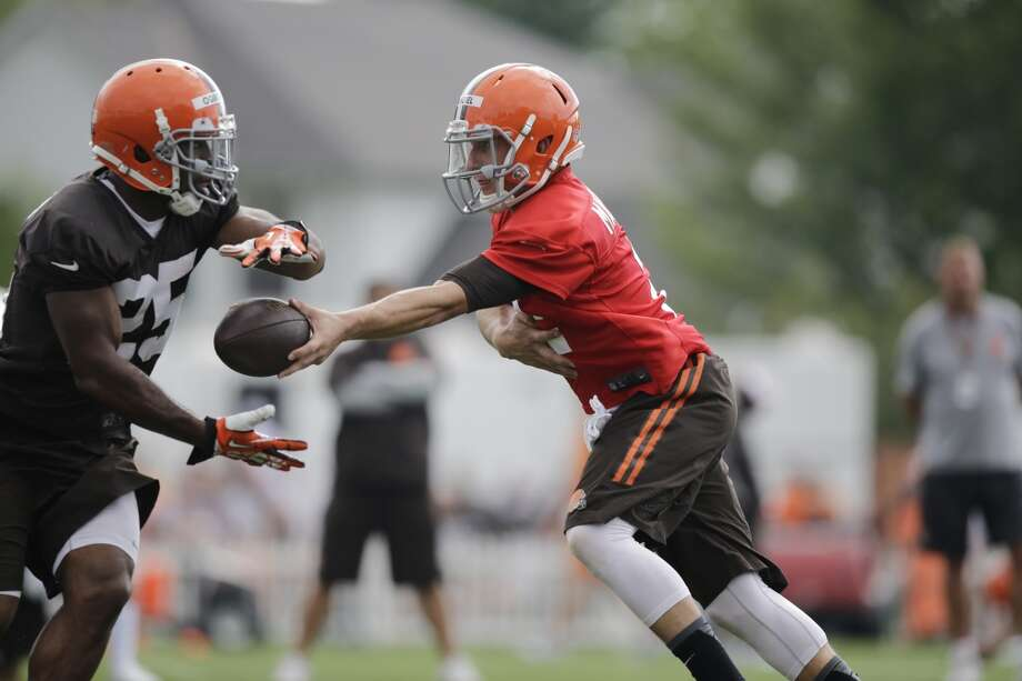 Cleveland Browns quarterback Johnny Manziel, right, hands off to running back Chris Ogbonnaya at the NFL football team's training camp in Berea, Ohio Saturday, July 26, 2014. Photo: Mark Duncan, Associated Press