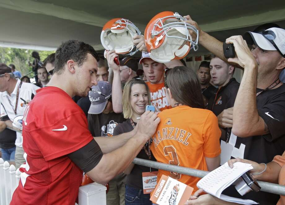 Cleveland Browns quarterback Johnny Manziel signs autographs for fans after his first practice at the NFL football team's training camp in Berea, Ohio on Saturday, July 26, 2014. Photo: Mark Duncan, Associated Press