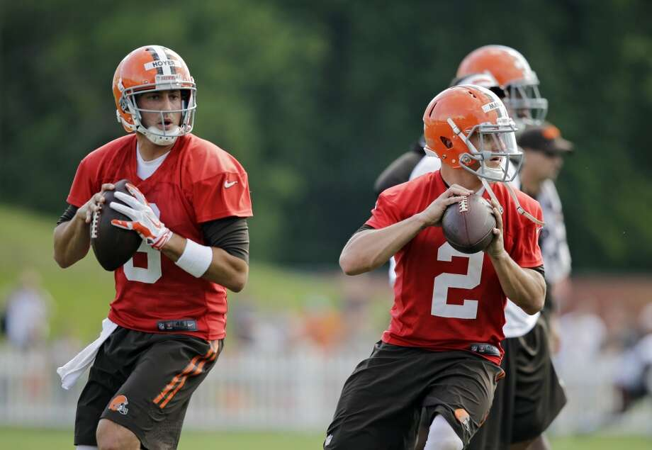 Cleveland Browns quarterback Brian Hoyer (6) and Johnny Manziel (2) drop back to pass during the opening practice at the NFL football team's training camp in Berea, Ohio Saturday, July 26, 2014. Photo: Mark Duncan, Associated Press