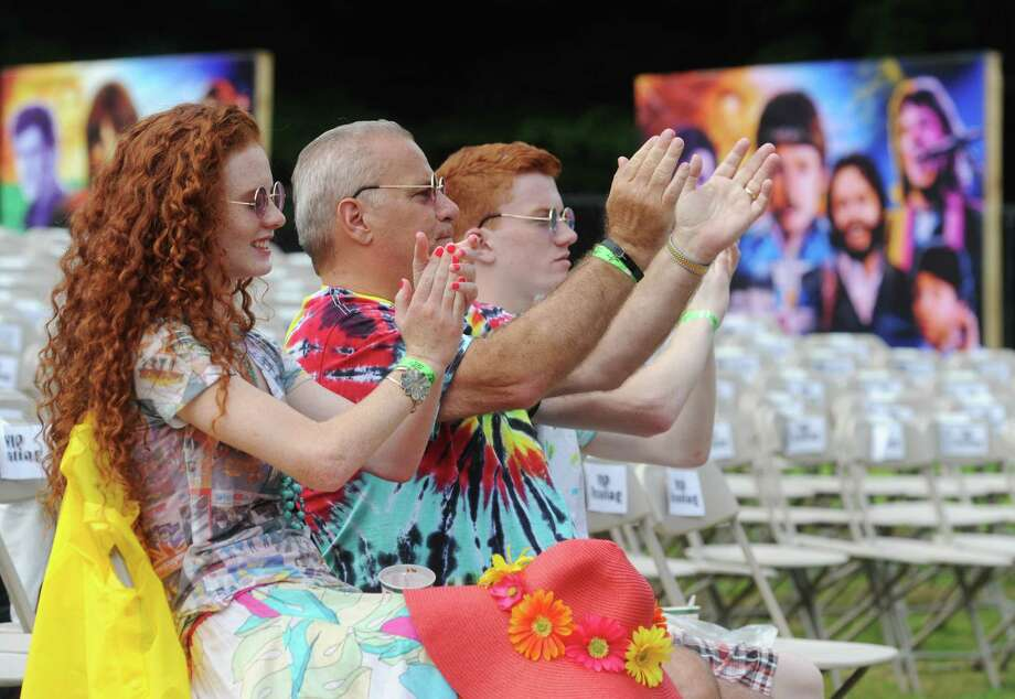 Kelsey Gangnath, left, Phil Gangnath, center, and Mikey Gangnath, of Trumbull, clap after hearing a song by a Beatles cover band during Danbury Fields Forever III at Ives Concert Park on the Western Connecticut State University Westside Campus in Danbury, Conn. Saturday, July 26, 2014.  The concert continues Sunday from noon until 8 p.m. with performances from 20 Beatles cover bands playing songs by the Fab Four in celebration of their 50th anniversary. Photo: Tyler Sizemore / The News-Times