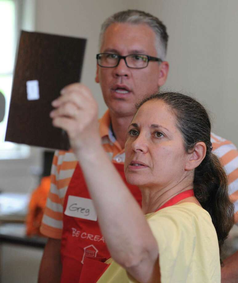 Greg Bouley, of West Hartford, and class helper Ellen Morrell examine a piece of glass during a glass bowl-making class at the Brookfield Craft Center in Brookfield, Conn. Saturday, July 26, 2014. Photo: Tyler Sizemore / The News-Times