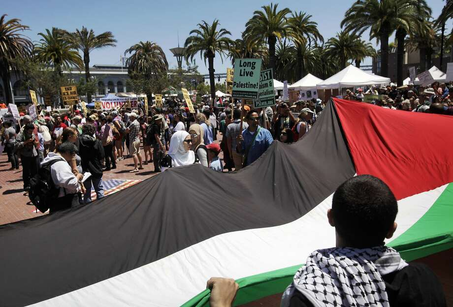 Omar Mogannam, 29, holds up a corner of a Palestinian flag during a rally and protest against the ongoing violence in Palestine organized by the Arab Resource and Organizing Center (AROC), the American Muslims for Palestine (AMP) and the ANSWER Coalition July 26, 2014 on the Embarcadero in San Francisco, Calif. Photo: Leah Millis, The Chronicle
