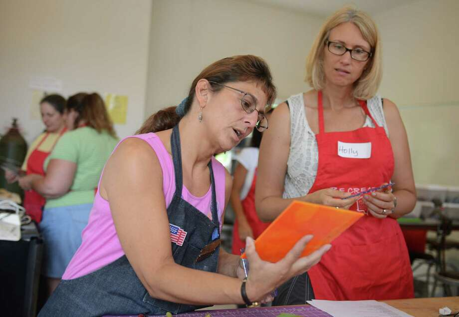 Class instructor Suzanna Pisano, left, and Holly Bouley, of West Hartford, examine an orange piece of glass during a glass bowl-making class at the Brookfield Craft Center in Brookfield, Conn. Saturday, July 26, 2014. Photo: Tyler Sizemore / The News-Times