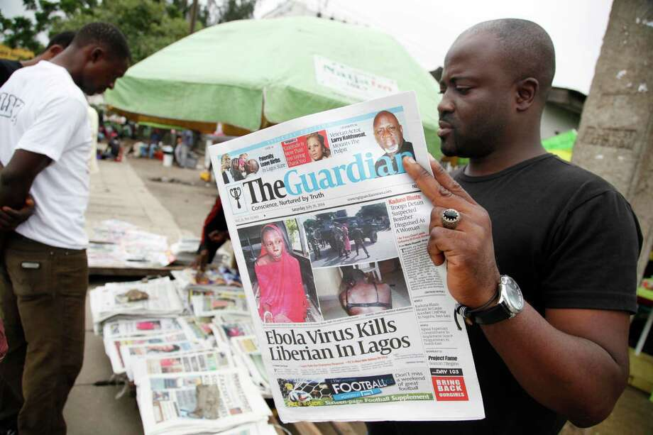 A man reads a local newspaperson a street with the headline Ebola Virus kills Liberian in Lagos, in Lagos Nigeria, Saturday, July 26, 2014. An Ebola outbreak that has left more than 600 people dead across West Africa has spread to the continent's most populous nation after a Liberian man with a high fever vomited aboard an airplane to Nigeria and then died there, officials said Friday. (AP Photo/Sunday Alamba)  The 40-year-old man had recently lost his sister to Ebola in Liberia, health officials there said. It was not immediately clear how he managed to board a flight, but he was moved into an isolation ward upon arrival in Nigeria on Tuesday and died on Friday. (AP Photo/Sunday Alamba) Photo: Sunday Alamba, STF / AP