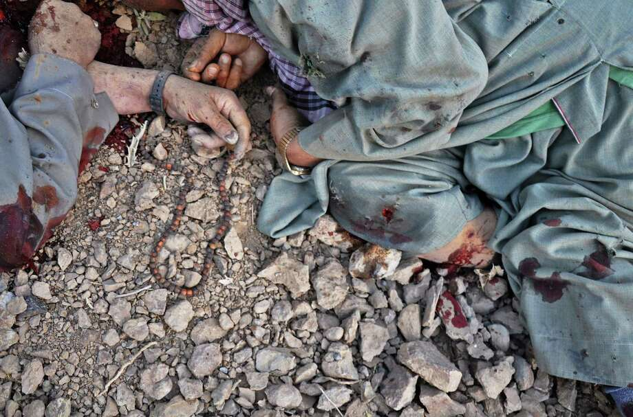 The dead bodies of Shiite civilians, one with fallen prayer beads nearby, are seen on the ground after Taliban insurgents stopped their bus on the road in the western Ghor province of Afghanistan, Friday, July 25, 2014. The militants halted minibuses, identified more than a dozen Shiite passengers and shot them dead by the side of the road overnight Friday, an official said. (AP Photo) ORG XMIT: GAH101 / AP