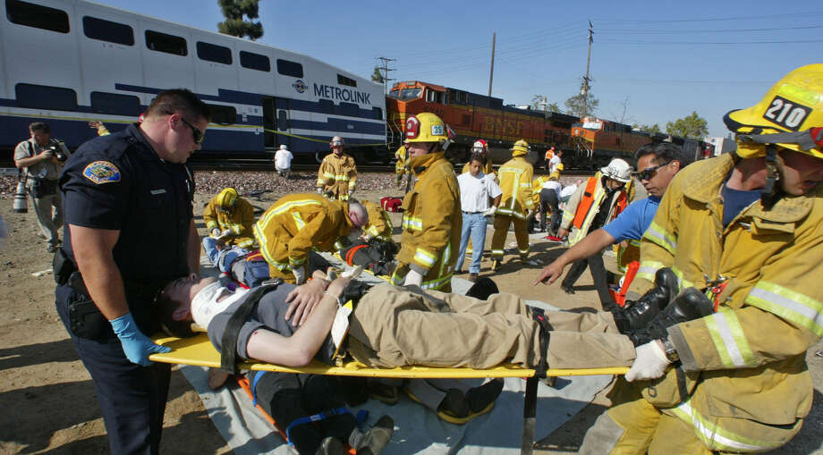 A fireman and police officer carry an injured passanger from the Metrolink commuter train to a triage area after the commuter train was struck head-on by a freight train during rush hour Tuesday, April 23, 2002, killing two people and injuring at least 260 people in Placentia, Calif. The northbound Burlington Northern Santa Fe freight train struck the southbound Metrolink train at 8:10 a.m. south of Los Angeles, buckling and derailing two cars packed with passengers. (AP Photo/Orange County Register, Jebb Harris) Photo: JEBB HARRIS / ORANGE COUNTY REGISTER