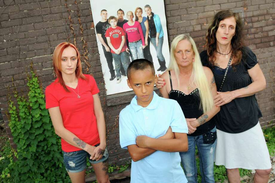 Photographer Brenda A. Kenneally, right, with Kayla Stocklas, left, her son DeAnthony Stocklas, 10, center, and her mother Debra Stocklas on Saturday, July 26, 2014, in Troy, N.Y. Behind them is one of Kenneally's images of the Stocklas family. She has been documenting the lives of her subjects since 2004. (Cindy Schultz / Times Union) Photo: Cindy Schultz / 00027942A