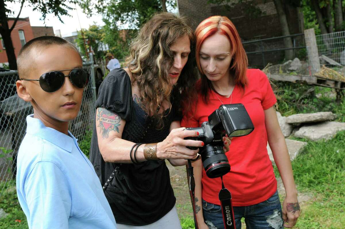 Photographer Brenda A. Kenneally, center, shows an image to Kayla Stocklas, right, and her son DeAnthony Stocklas, 10, on Saturday, July 26, 2014, in Troy, N.Y. Kenneally has been documenting the lives of her subjects since 2004. (Cindy Schultz / Times Union)