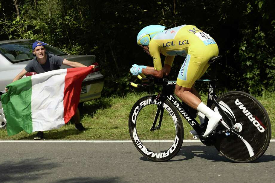 Italy's Vincenzo Nibali wearing the overall leader's yellow jersey rides past a supporter holding an Italian national flag during the twentieth stage, a 54 km individual time trial, as part of the 101st edition of the Tour de France cycling race on July 26, 2014 between Bergerac and Perigueux, western France.  AFP PHOTO / LIONEL BONAVENTURELIONEL BONAVENTURE/AFP/Getty Images ORG XMIT: 496135977 Photo: LIONEL BONAVENTURE / AFP