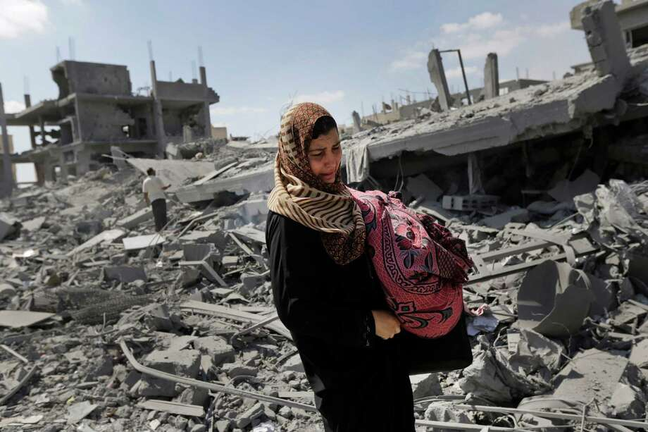 A Palestinian woman carries her belongings past the rubble of houses destroyed by Israeli strikes in Beit Hanoun, northern Gaza Strip, Saturday, July 26, 2014. Thousands of Gaza residents who had fled Israel-Hamas fighting streamed back to devastated border areas during a lull Saturday, and were met by large-scale destruction: scores of homes were pulverized, wreckage blocked roads and power cables dangled in the streets. (AP Photo/Lefteris Pitarakis) Photo: Lefteris Pitarakis, STF / AP