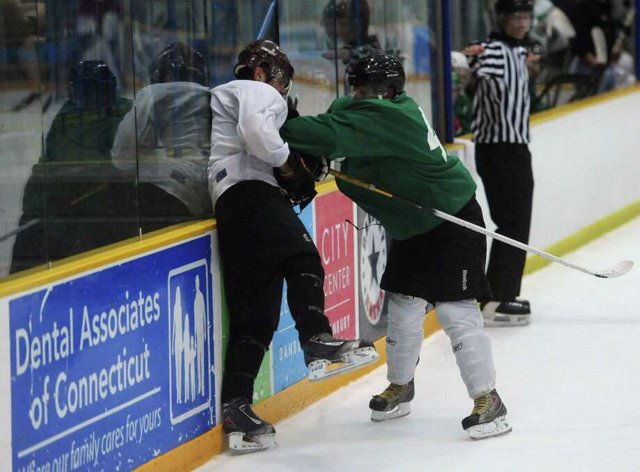White's Anthony LoBionco, left, gets checked into the boards by Green's Joseph Broderick in the Danbury Whalers' Fifth Annual Summer All-Star Game at the Danbury Ice Arena in Danbury, Conn. Saturday, July 26, 2014. Photo: Tyler Sizemore / The News-Times