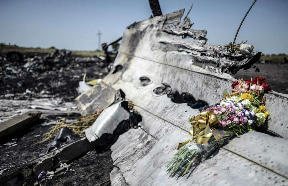 This photo taken on July 26, 2014 shows flowers, left by parents of an Australian victim of the crash, laid on a piece of the Malaysia Airlines plane MH17, near the village of Hrabove (Grabovo), in the Donetsk region. Ukraine sought on July 25 to avoid a political crisis after the shock resignation of its prime minister, as fighting between the army and rebels close to the Malaysian airliner crash site claimed over a dozen more lives. Dutch and Australian forces were being readied on July 26 for possible deployment to secure the rebel-held crash site of the Malaysia Airlines flight MH17 in east Ukraine where many victims' remains still lie nine days after the disaster claimed 298 lives. AFP PHOTO/ BULENT KILICBULENT KILIC/AFP/Getty Images ORG XMIT: - Photo: BULENT KILIC / AFP