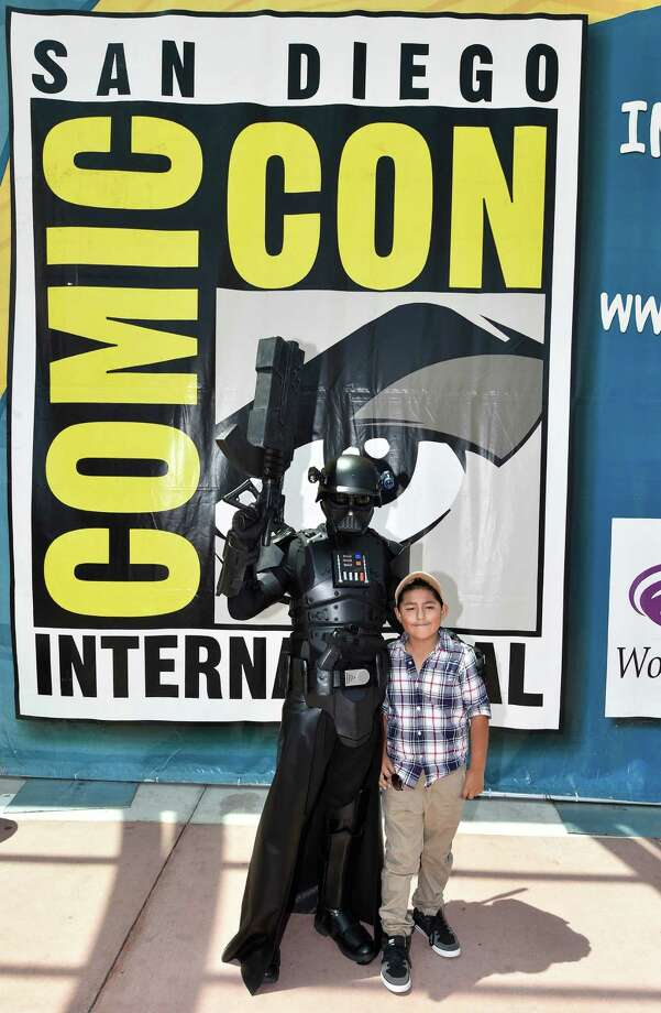 Star Wars' Darth Vader Luis Linares poses with a fan outside of the convention center on Day 3 at the 2014 Comic-Con International Convention held Saturday, July 26, 2014, in San Diego. Photo: Denis Poroy, Denis Poroy/Invision/AP / Invision