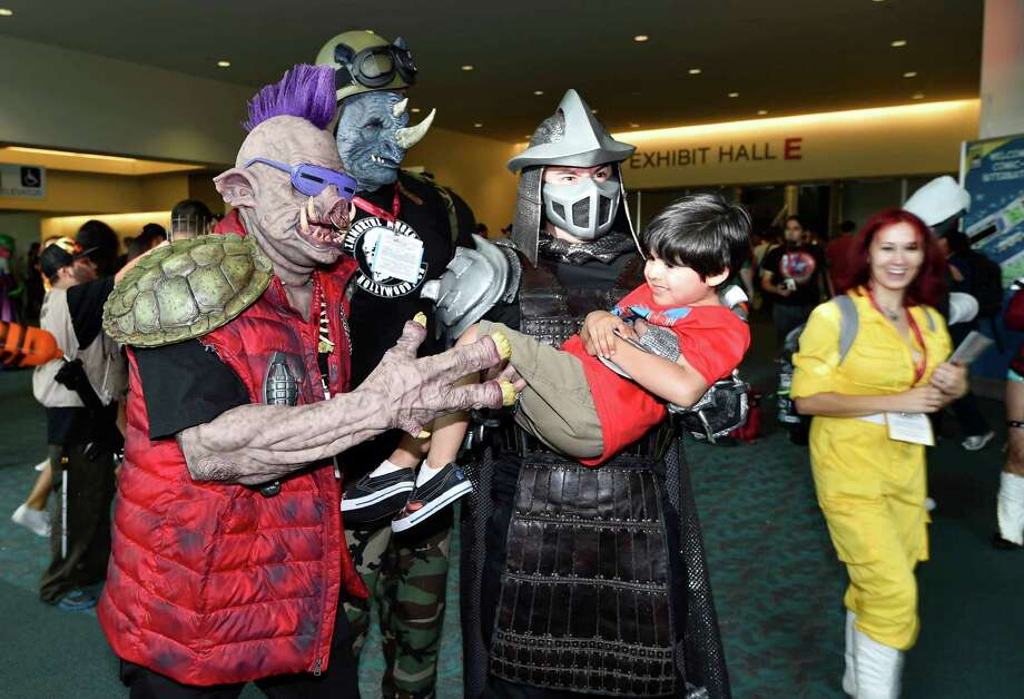 Characters from the Teenage Mutant Ninja Turtles hold Aaron Garcia, 4, for a photo on day three at the 2014 Comic-Con International Convention held Saturday, July 26, 2014 in San Diego. Photo: Denis Poroy, Denis Poroy/Invision/AP / Invision