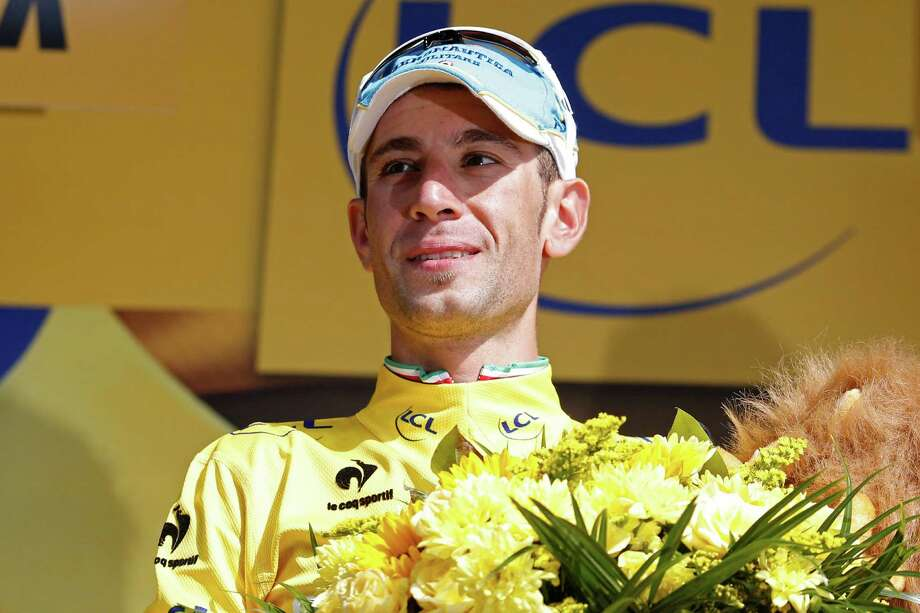 Italy's Vincenzo Nibali, wearing the overall leader's yellow jersey, celebrates on the podium of the twentieth stage of the Tour de France cycling race, an individual time-trial over 54 kilometers (33.6 miles) with start in Bergerac and finish in Perigueux, France, Saturday, July 26, 2014. (AP Photo/Christophe Ena) Photo: Christophe Ena, STF / AP