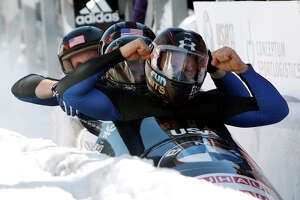 United States' pilot Steven Holcomb, right, with pushers Justin Olsen, Steven Langton and brakeman Curtis Tomasevicz, react after winning the men's four-man Bobsled World Championships in Lake Placid, N.Y., on Sunday, Feb. 26, 2012. (AP Photo/Mike Groll)