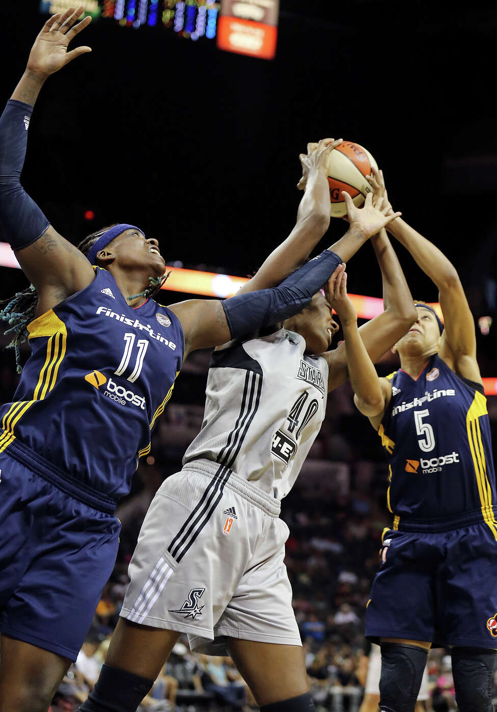 San Antonio Stars' Kayla Alexander grabs for a rebound between Indiana Fever's Lynetta Kizer (left) and Layshia Clarendon during first half action Saturday July 26, 2014 at the AT&T Center.