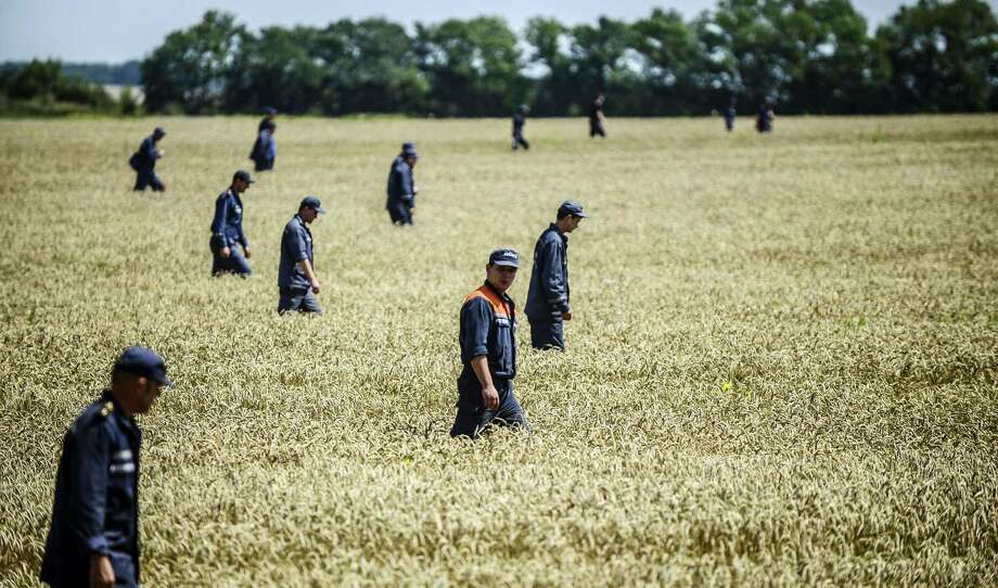 Members of the  Ukrainian State Emergency Service search for bodies in a field near the crash site of Malaysia Airlines Flight MH17 on Saturday. Photo: BULENT KILIC, Staff / AFP
