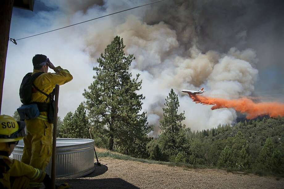 A DC-10 Air Tanker makes a drop on the Sand Fire at the middle fork of the Cosumnes River in Northern California as firefighters standby to protect a home on Saturday, July 26, 2014. Hundreds of firefighters are working in rugged terrain and triple-digit temperatures. (AP Photo/The Sacramento Bee, Hector Amezcua) MAGS OUT; LOCAL TV OUT (KCRA3, KXTV10, KOVR13, KUVS19, KMAZ31, KTXL40); MANDATORY CREDIT: THE SACRAMENTO BEE, HECTOR AMEZCUA Photo: Hector Amezcua, Associated Press