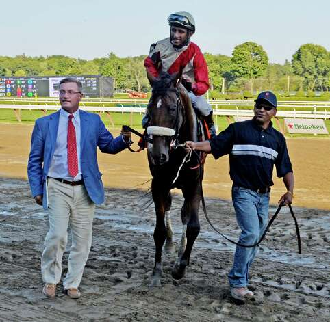 Wicked Strong with jockey Rajiv Maragh lead to the winner's circle by Centennial Farm's president Donald Little Jr., left, after winning the 51st running of the Jim Dandy Saturday afternoon July 26, 2014 at the Saratoga Race Course in Saratoga Springs, N.Y.    (Skip Dickstein / Times Union) Photo: SKIP DICKSTEIN