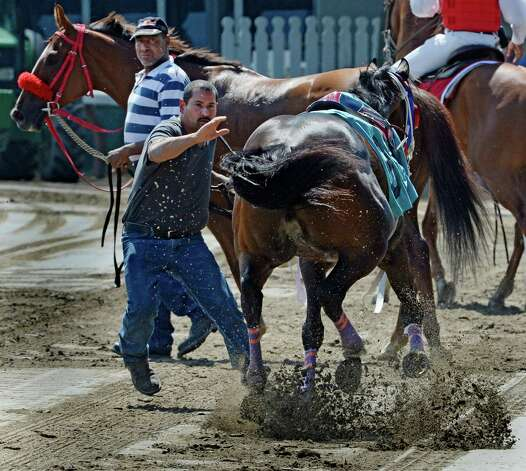 A groom tries to stop Two Blue who dropped his rider after the fourth race of the day Saturday afternoon July 26, 2014 at the Saratoga Race Course in Saratoga Springs, N.Y.    (Skip Dickstein / Times Union) Photo: SKIP DICKSTEIN