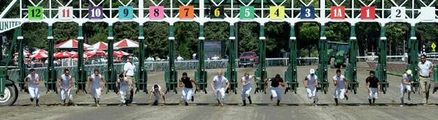 Thirteen jockeys lined up to run in a foot race as a fund raiser for the Permanently Disabled Jockeys Fund  Saturday afternoon July 26, 2014 at the Saratoga Race Course in Saratoga Springs, N.Y.  The winner was #4 jockey Luis Saez  (Skip Dickstein / Times Union) Photo: SKIP DICKSTEIN