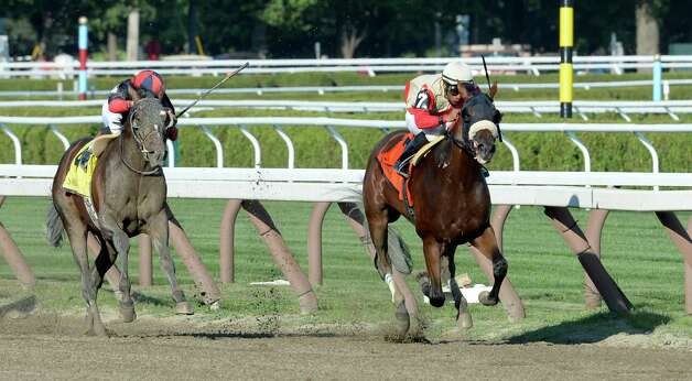 Wicked Strong with jockey Rajiv Maragh, right, runs away from Belmont Stakes winner Tonalist with jockey Joel Rosario to win the 51st running of the Jim Dandy Saturday afternoon July 26, 2014 at the Saratoga Race Course in Saratoga Springs, N.Y.    (Skip Dickstein / Times Union) Photo: SKIP DICKSTEIN