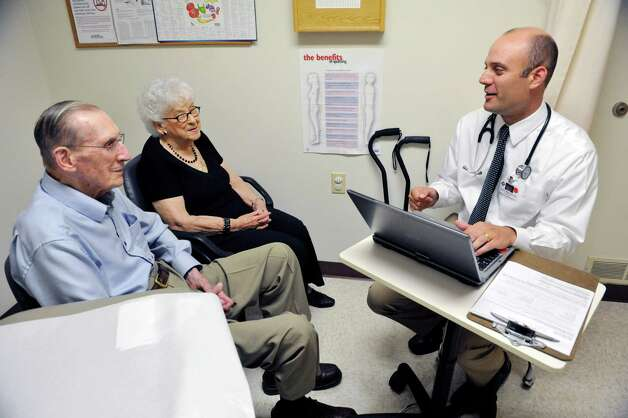 Husband and wife, Bob and Margaret Putnam, meet with Dr Tucker Slingerland, lead provider at Moreau Family Health Center during a checkup visit for Bob on on Monday, July 21, 2014, in South Glens Falls, N.Y.  The couple, who are both 93 years old, have been patients of Dr. Slingerland for the past five years.  (Paul Buckowski / Times Union) Photo: Paul Buckowski / 00027852A
