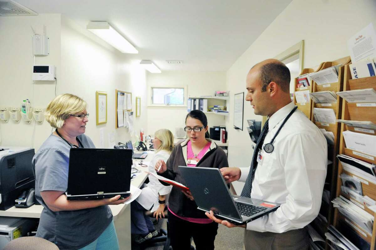 R.N. Jennifer Vincent, left, a tele-health nurse and Brianne Balfour, center, a medical assistant talk with Dr. Tucker Slingerland, lead provider, about patient care at Moreau Family Health Center on Monday, July 21, 2014, in South Glens Falls, N.Y. Vincent is one of two nurses that perform the initial triage of patients when they call in, making the decision on what the next step should be.