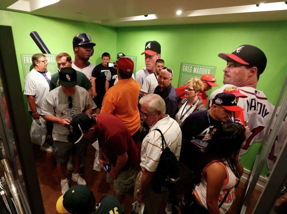 Fans visit displays of Frank Thomas, Tom Glavine and Greg Maddux at the Baseball Hall of Fame on Saturday, July 26, 2014, in Cooperstown, N.Y. The former Major League Baseball players will be inducted to the hall on Sunday. (AP Photo/Mike Groll) ORG XMIT: NYMG110 Photo: Mike Groll / AP