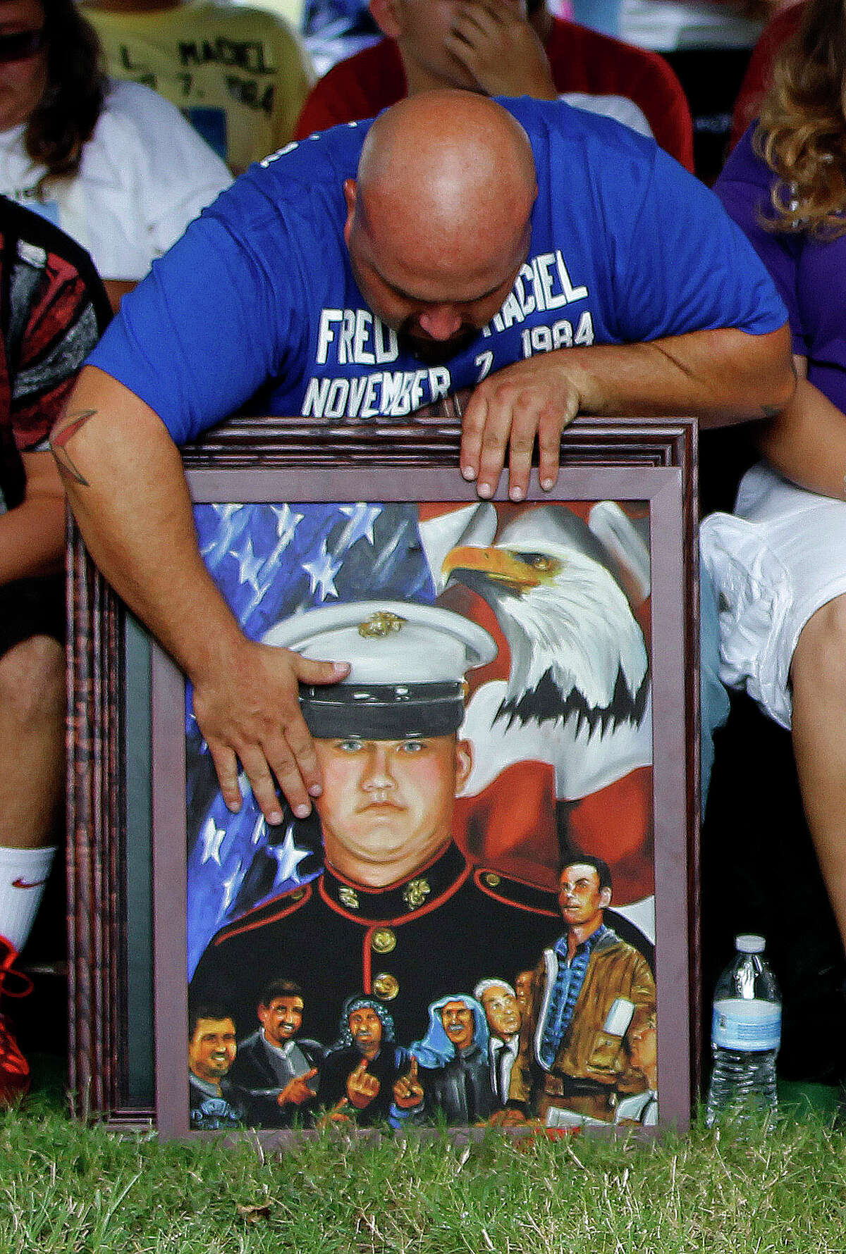 Lee Nelson, cousin of Fred Maciel, who died in Iraq, hugs a Ken Pridgeon Sr. painting of him on Saturday.