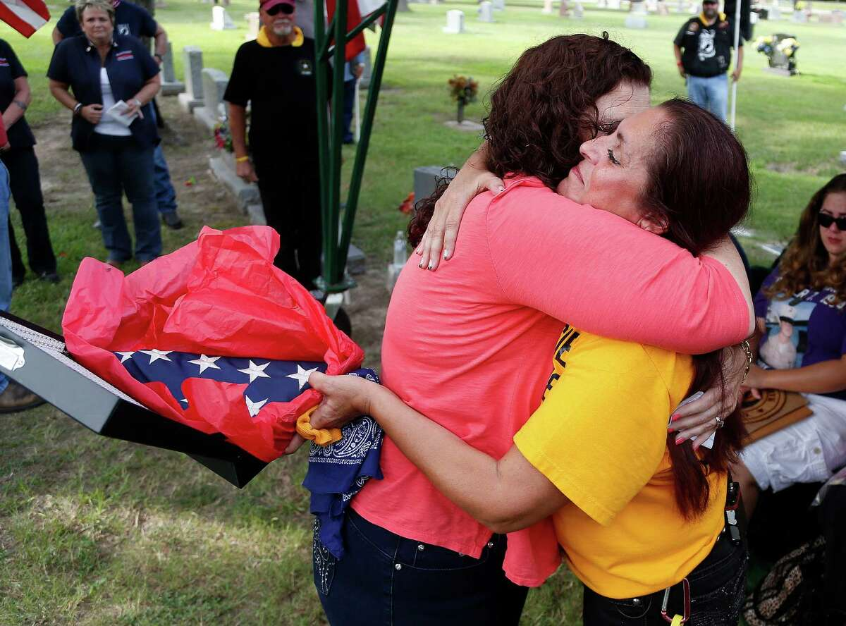 Patsy Maciel, the mother of Fred Maciel, who died in a helicopter crash in Iraq, hugs Lanie Brown as she holds her son's flag at Calvary Hill Cemetery on Aldine Westfield Road on Saturday.
