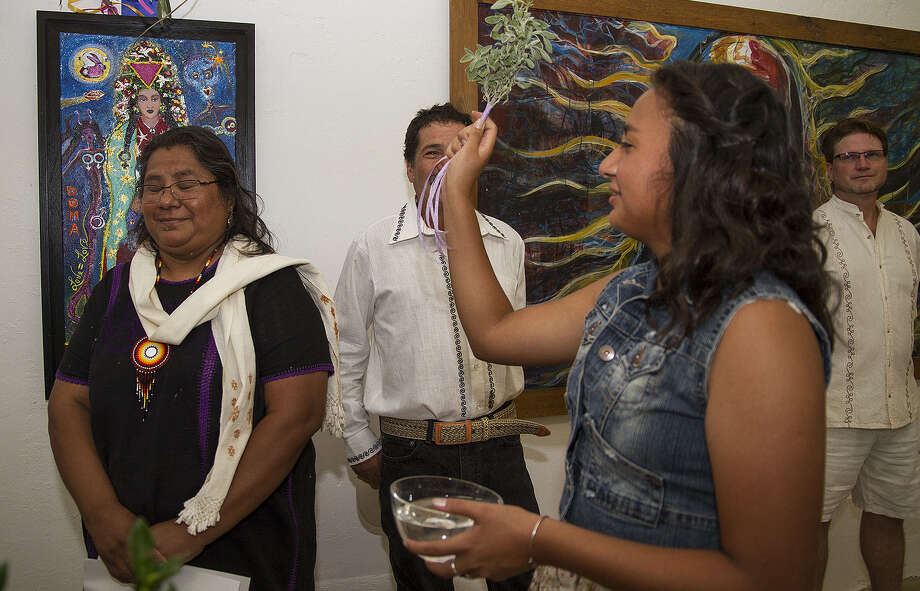 Veronica Alfonsina Castillo, 16, blesses her mom, Veronica Castillo, at the inaugural exhibition at Eco y Voces del Arte. Photo: Alma E. Hernandez / For The San Antonio Express-News