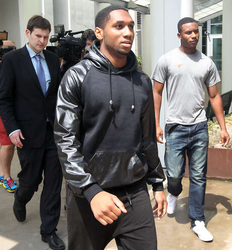 UT-Austin football players Kendall Sanders (front) and Montrel Meander (right) leave the Travis County Criminal Justice Center after being booked Thursday. Photo: Ralph Barrera / Statesman.com / Austin American-Statesman