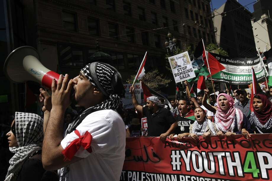 Sam Iyesh, 20, left, with Arab Youth Organization, leads chants on a bullhorn during a protest march down Market and through downtown following a rally against the ongoing violence in Palestine organized by the Arab Resource and Organizing Center (AROC), the American Muslims for Palestine (AMP) and the ANSWER Coalition July 26, 2014 in San Francisco, Calif. Photo: Leah Millis, The Chronicle