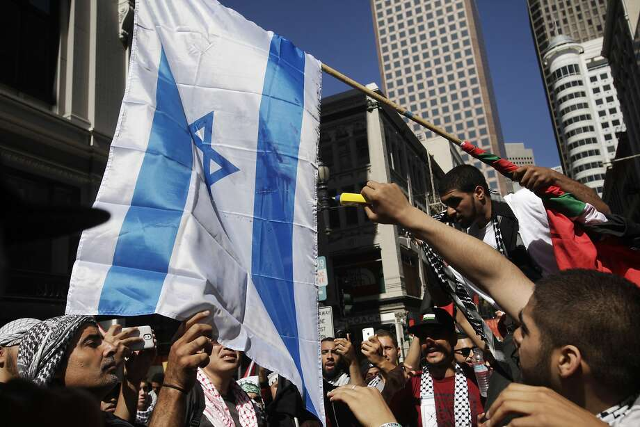 Protesters douse an Israeli flag with lighter fluid before setting it ablaze during a protest march down Market and through downtown following a rally against the ongoing violence in Palestine organized by the Arab Resource and Organizing Center (AROC), the American Muslims for Palestine (AMP) and the ANSWER Coalition July 26, 2014 in San Francisco, Calif. Photo: Leah Millis, The Chronicle
