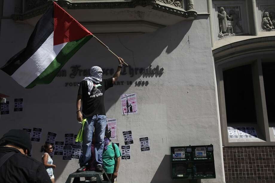 "A protester waves a Palestinian flag outside of the San Francisco Chronicle as protesters linger outside of the building, chanting about the paper's ""lies"" as part of a march through downtown following a rally against the ongoing violence in Palestine organized by the Arab Resource and Organizing Center (AROC), the American Muslims for Palestine (AMP) and the ANSWER Coalition July 26, 2014 in San Francisco, Calif. Photo: Leah Millis, The Chronicle"