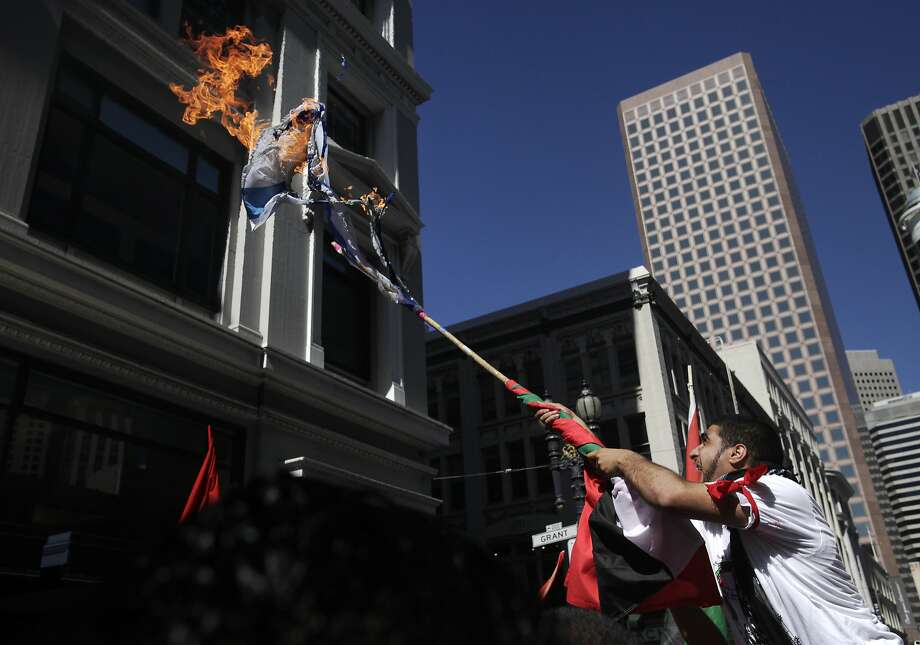 Protesters cheer as they burn an Israeli flag during a protest march down Market and through downtown following a rally against the ongoing violence in Palestine organized by the Arab Resource and Organizing Center (AROC), the American Muslims for Palestine (AMP) and the ANSWER Coalition July 26, 2014 in San Francisco, Calif. Photo: Leah Millis, The Chronicle