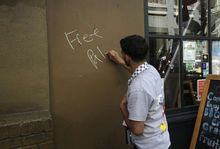 "Saleh Abdallah, 18, writes ""Free Palestine"" with chalk on the wall of a downtown business during a protest march down Market and through downtown following a rally against the ongoing violence in Palestine organized by the Arab Resource and Organizing Center (AROC), the American Muslims for Palestine (AMP) and the ANSWER Coalition July 26, 2014 in San Francisco, Calif. Photo: Leah Millis, The Chronicle"