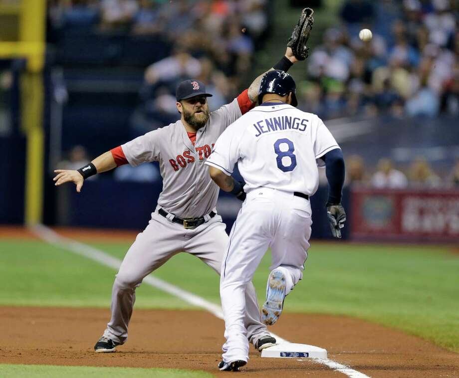 Boston Red Sox first baseman Mike Napoli can't hang on to a wild throw from catcher Christian Vazquez on a bunt by Tampa Bay Rays' Desmond Jennings during the first inning of a baseball game Saturday, July 26, 2014, in St. Petersburg, Fla. Jennins made it all the way to third. Vazquez was charged with an error. (AP Photo/Chris O'Meara)  ORG XMIT: SPD101 Photo: Chris O'Meara / AP