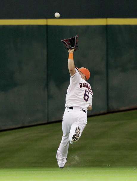 Astros center fielder Kiké Hernandez, who had a costly error Friday, redeemed himself with this  over-the-shoulder catch in the second inning of Saturday's loss to the Marlins at Minute Maid Park. Photo: Bob Levey, Stringer / 2014 Getty Images