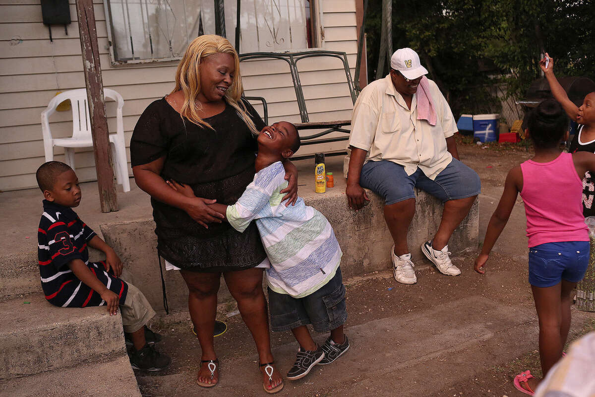 Tamika Winn is embraced by son, Trezvant Mason, 7, as they spend the evening with family at the East Side home owned by Winn's grandmother, Gloria Nelson.
